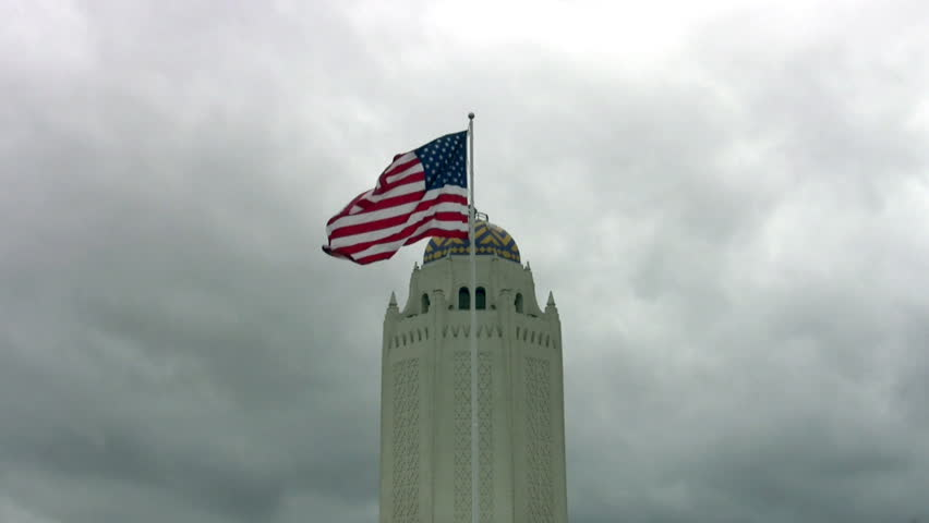 Video closeup of water tower and US flag at Randolph AFB, San Antonio, Texas. Taj Mahal due to it's design. Military building in Texas. Cloudy and windy day with flag waving and clouds moving.   - HD stock video clip