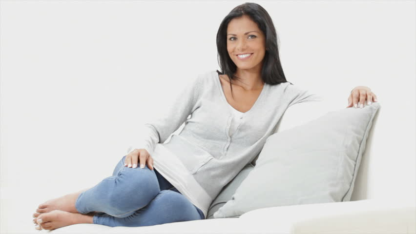 Beautiful young woman sitting on the sofa at home. Relaxed woman with long black hair in living room sitting on couch. Smiling girl relaxing at home and looking at camera. - HD stock video clip