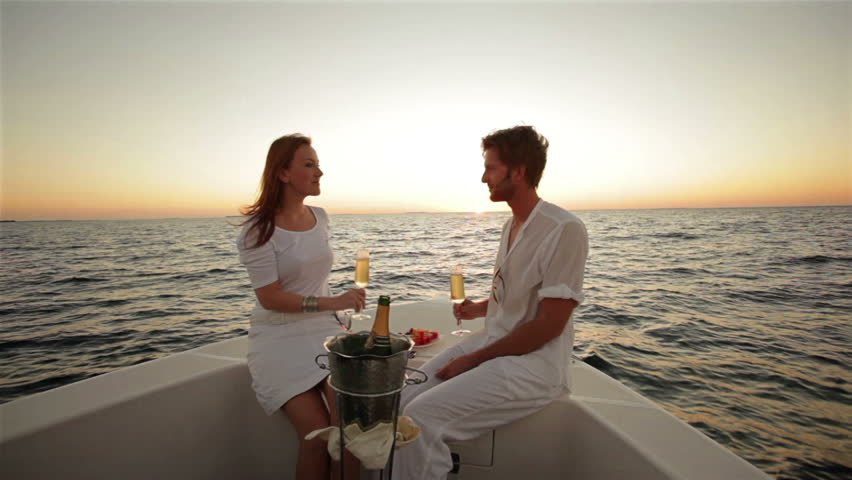 young honeymoon couple drinking champagne on a boat at sunset