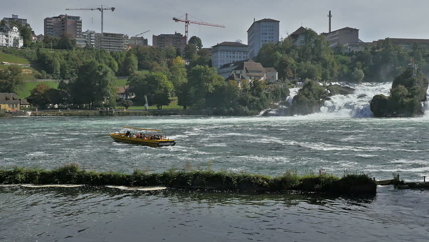 Yellow tour boat on the Rhine river below the Rhine Falls in Switzerland with city buildings in background.  - HD stock footage clip