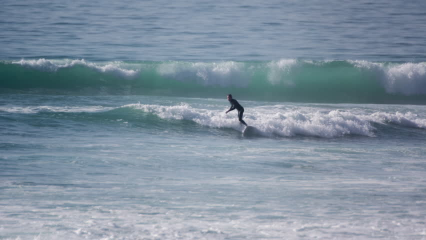 a surfer in the water at taghazout on the atlantic coast of morocco. this area of coast is world renowned for its surfing