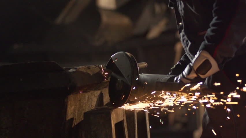 Slow Motion Of Worker Cutting Metal With Circular Saw With Sparks Flying About