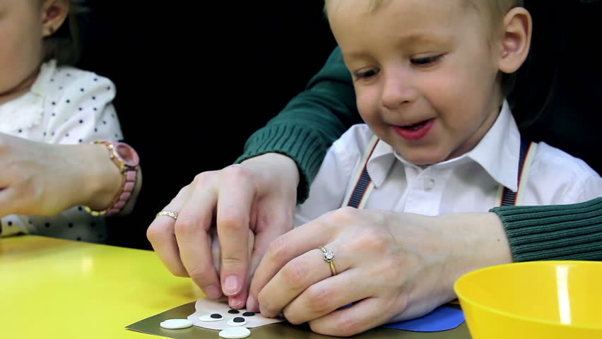 Small children and their mothers engaged in the development of intelligence. Boy plays with clay