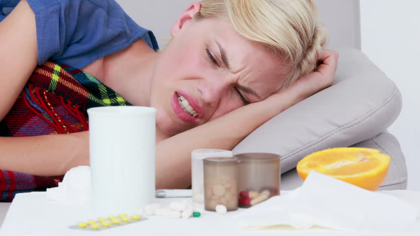 Sick woman blowing his nose while he is lying on bed with pills on the bedside table
