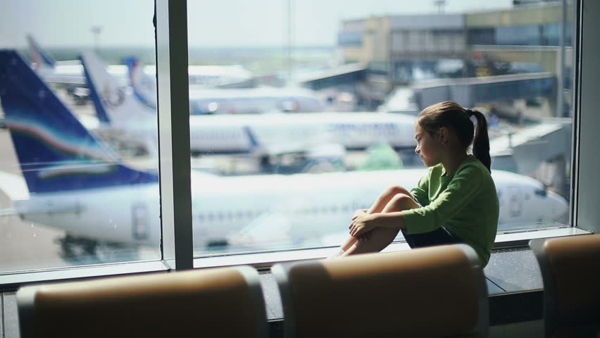 Child at the airport near the window looking at airplanes and waiting for time of flight