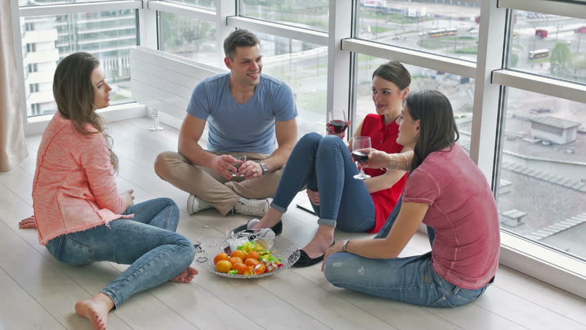 Friends sitting on the floor and drinking wine  - HD stock footage clip
