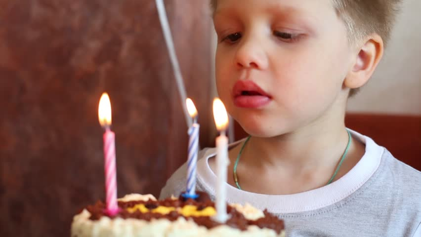 Happy handsome boy blows out three candles on birthday cake