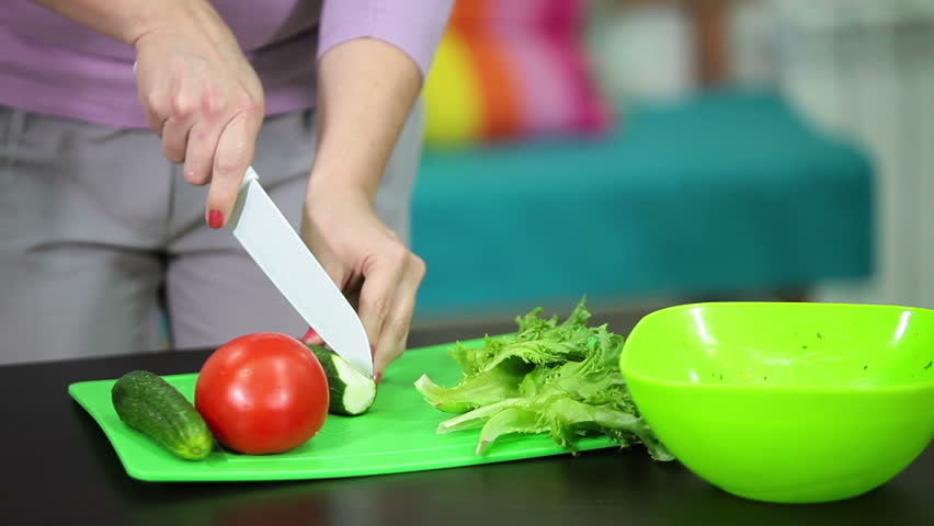 Slicing Cucumber On A Green Cutting Board In The Kitchen