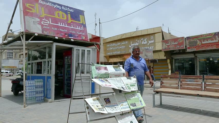 BAGHDAD, IRAQ - MAY 2015: Iraqi man picks a newspaper to read it at Palestine street in Baghdad, Iraq