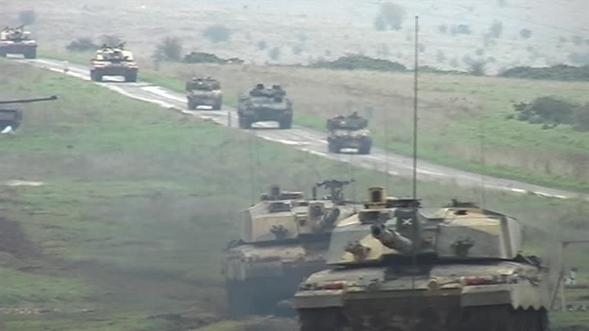Military tanks driving along a road. Handheld shot. Shot in letterboxed 16:9 - SD stock footage clip