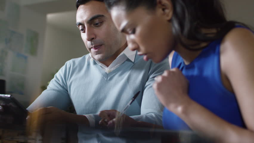 4k Two multi-ethnic professionals discussing figures on a computer tablet