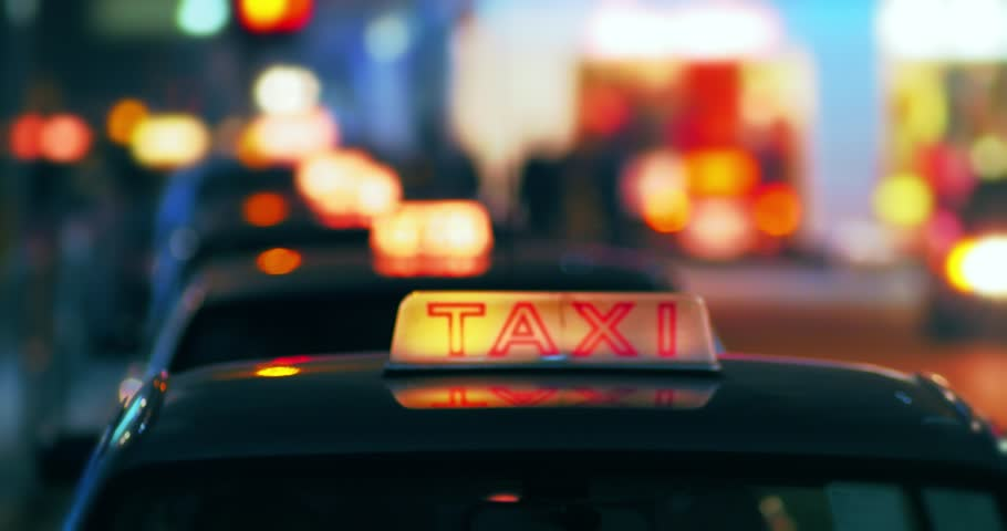 Bright night colors of city downtown. Lit taxi sign on car roof with defocused background of street in Hong Kong