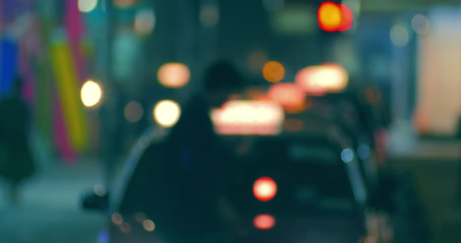 Blurred off focus background of city street at night with passenger entering in taxi cab