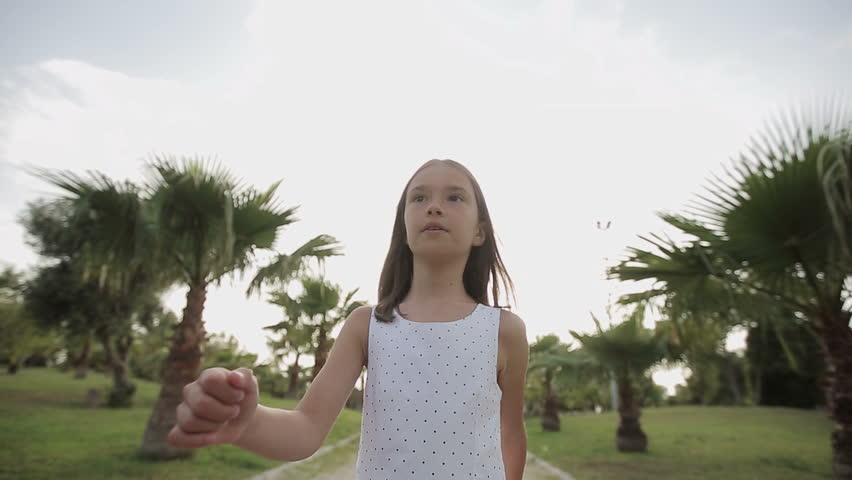 Child walks through a palm alley at sunset, rejoices and sings