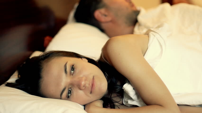 Unhappy woman lying in bed, man in the background - HD stock video clip