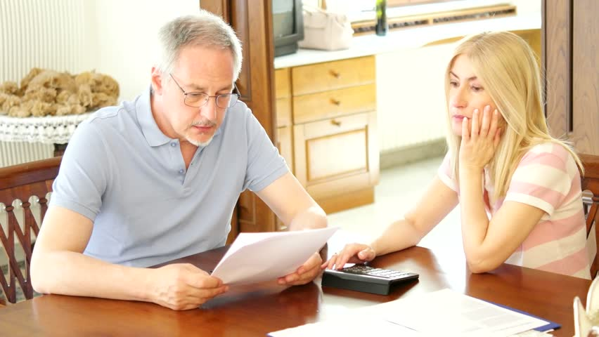 Mature couple checking finances while looking at bills - 4K stock footage clip