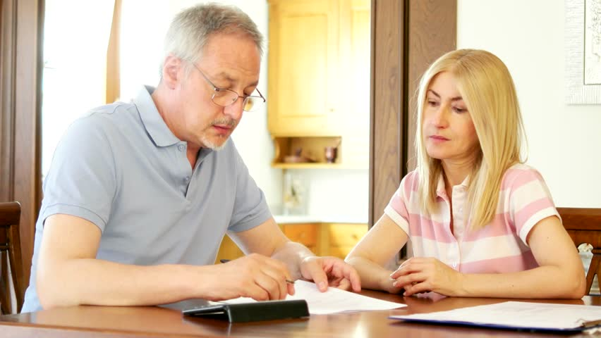 Mature couple checking finances while looking at bills - 4K stock video clip