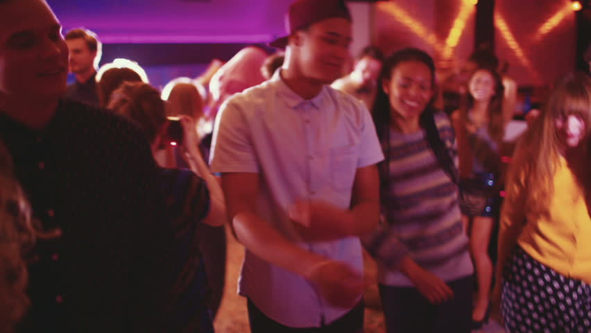 Smiling hipster friends dancing together at a party
