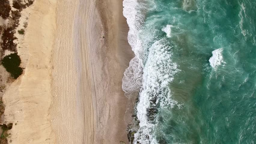 Aerial: Top shot sea moving down.