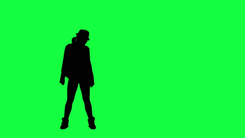 Silhouette of a girl in the hat dancing. Chroma key background. Silhouette of a woman dancing against a green background