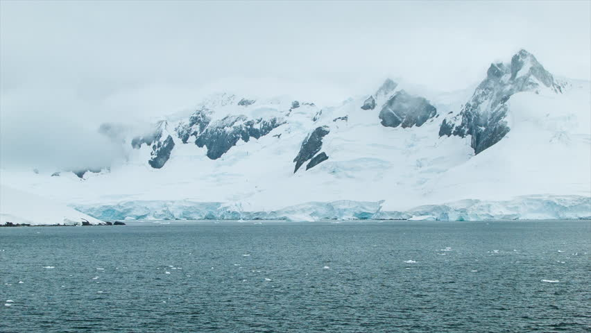 Freezing Cold Antarctica with Tall Ice Covered Mountains and Moving Southern Ocean Water