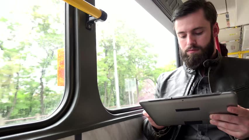 young handsome hipster man travel by tram and works on tablet