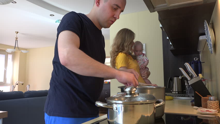 young family preparing lunch. Father cook soup in pot, mother with baby girl take fruit from the refrigerator. Family routine at home. Static tripod shot. 4K UHD video clip. - 4K stock footage clip