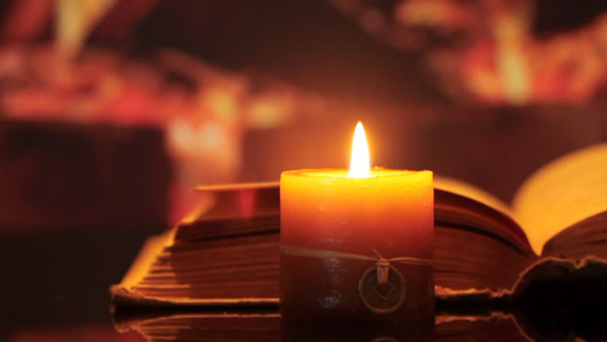 Candle in open book against background of fire. dolly shot.