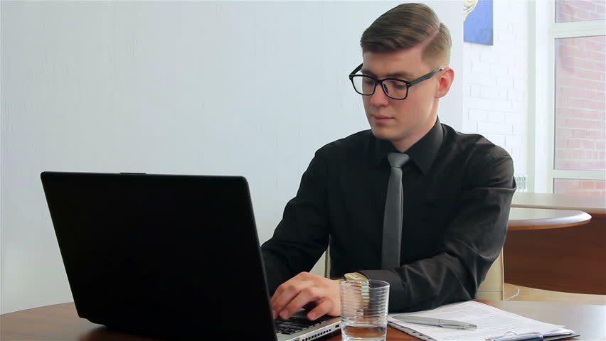 Young man working on laptop in a office. Businessman typing on laptop