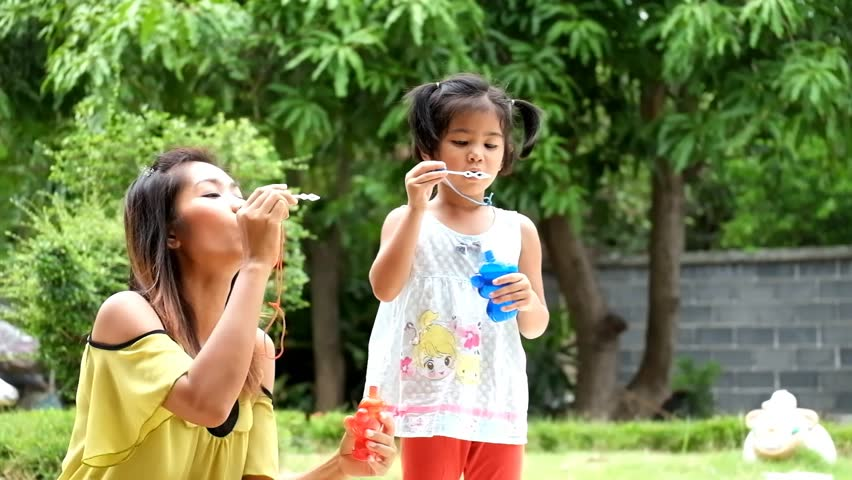 mother and daughter are blowing a soap bubbles, cute asian girl and mother playing soap bubbles - HD stock footage clip