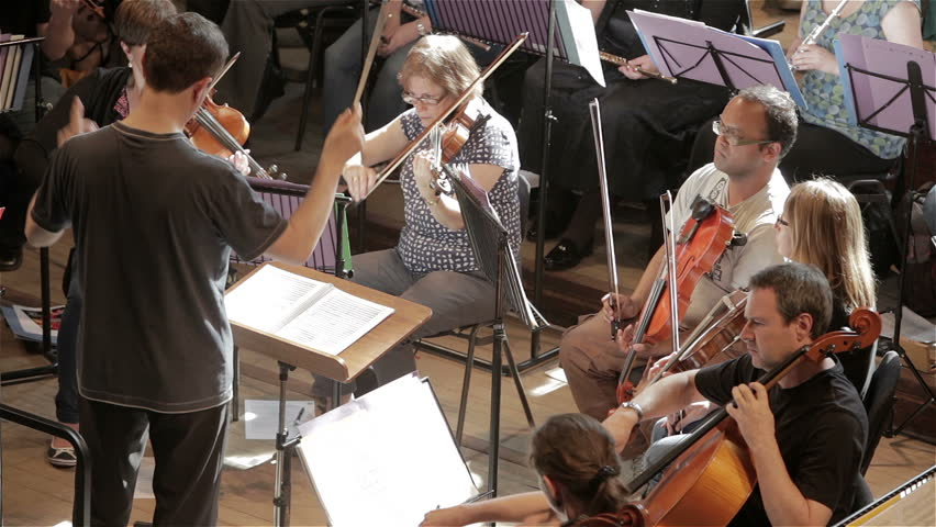 LONDON, UK - 8 JUNE 2013: Candid video footage of a conductor leading a classical orchestral rehearsal with the front desk second violins and violas in front of him.