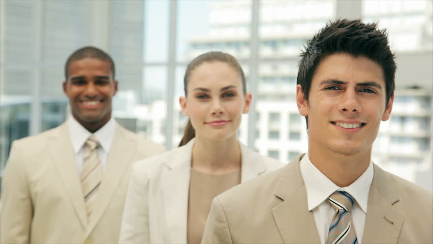 Panning shot of young businessman smiling with coworkers. Young business people are in formals. Multi-ethnic male and female professionals are in brightly lit office.