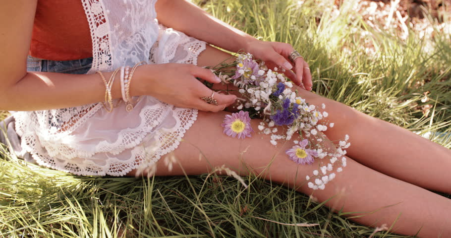 Cropped shot of a girl's hands holding flowers in lush green grass