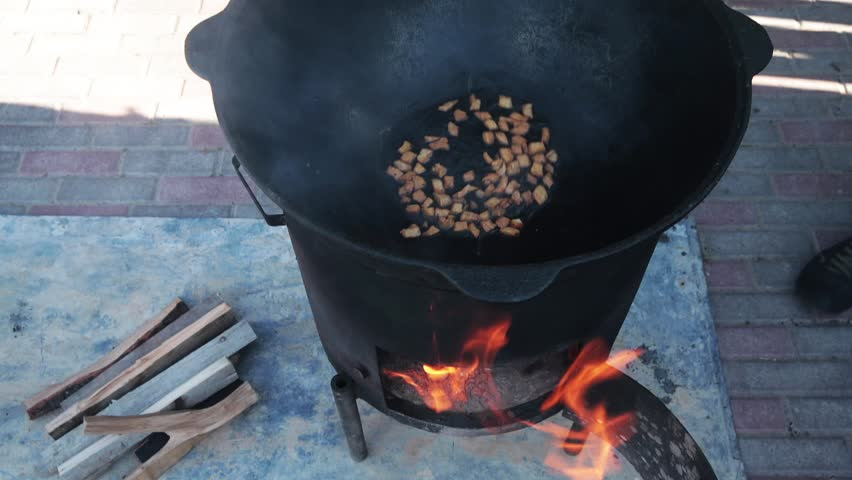 Uzbek national dish pilaf in a large cast-iron cauldron on the fire, the cooking process, fried pieces of fat tail, basis ??constituting food rice, lamb, carrot, mutton fat, sesame oil, onion, garlic - HD stock footage clip