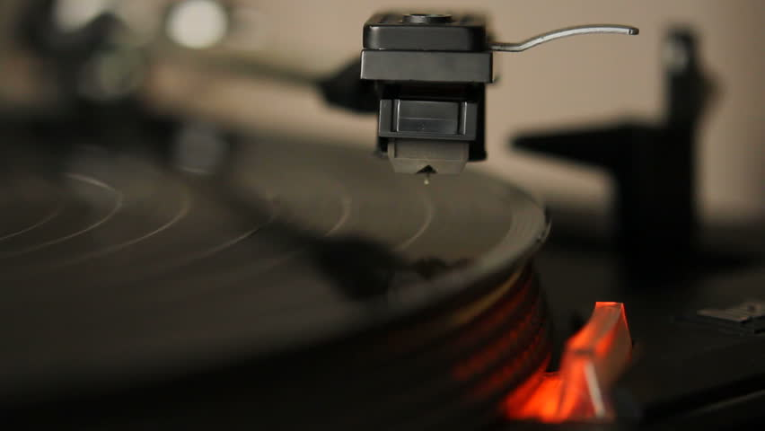 Close up HD movie of a record player playing a vinyl black record.