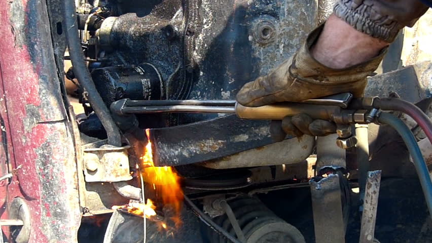 Welder cutting metal with a flame outdoors.Unrecognizable person, close up, slow motion , high speed camera