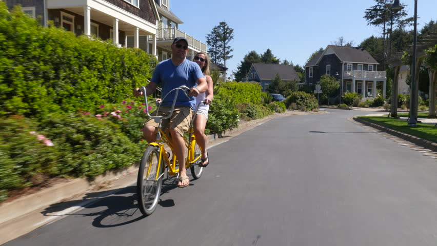 Couple riding tandem bicycle together in coastal vacation community