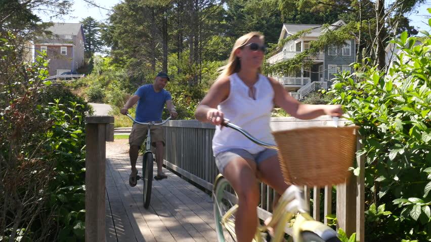 Couple riding bicycles across bridge