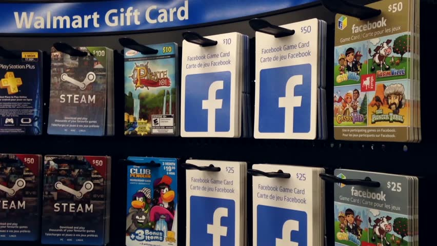 Coquitlam, BC, Canada - August 20, 2015 : Woman picking ten dollar facebook game gift card inside supermarket