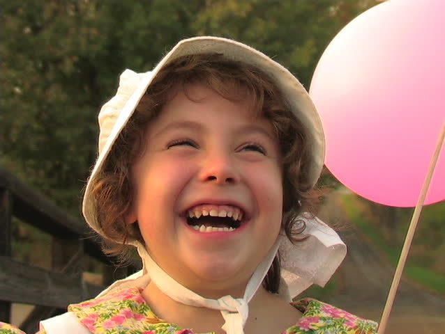 A YOUNG GIRL DRESSED IN A PIONEER COSTUME LAUGHS WHILE HOLDING A BALLOON. - SD stock footage clip