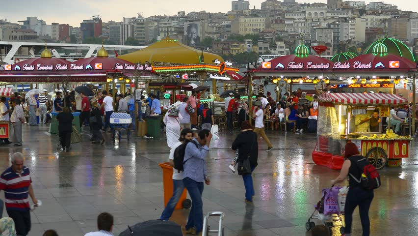 ISTANBUL - JUN 16, 2015: Rain in Istanbul. Crowd of people arrive and depart from Eminonu Pier looking to Goldenhorn and Galata Tower. 4K.  Hustle and bustle of people just before the rain started