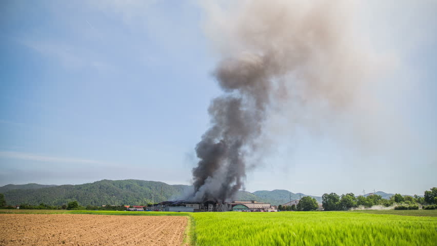 Smoke spreading and twisting in to blue sky timelapse 4K. Massive smoke from a warehouse on fire rising in to the sky with wind blowing it around. Green and farm field in front.
