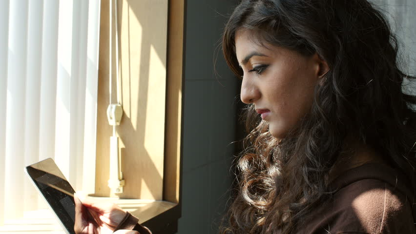Portrait of a middle eastern woman using a tablet in the window light