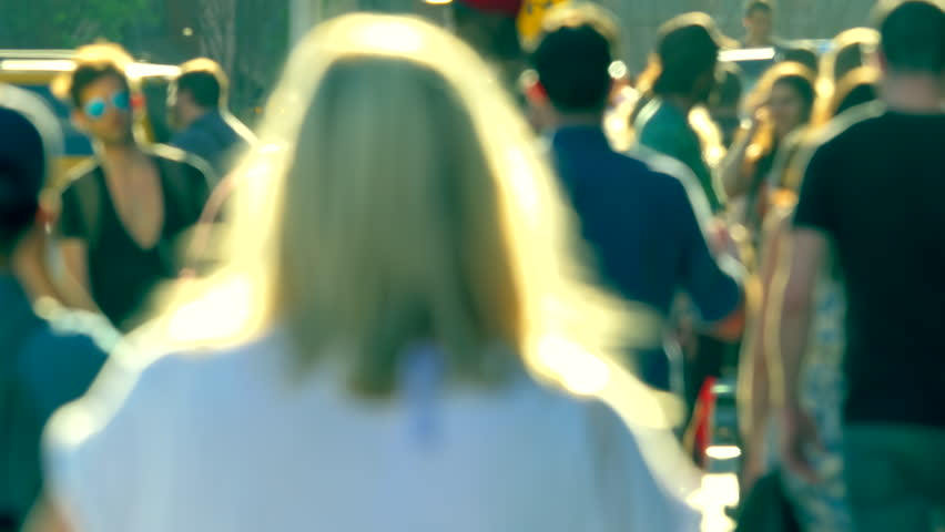 Unrecognisable anonymous crowd people pedestrians walking backlight defocused sunny day Manhattan New York City NYC