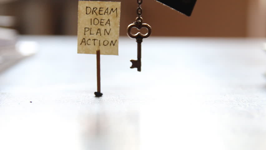 Golden key on a chain, and a label with the words: dream, idea, plan, action.