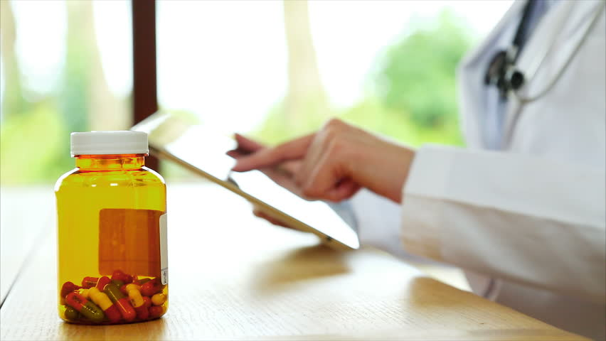 Rack focus of pill bottle with female doctor's hands using tablet computer. Professional is scrolling and zooming. She is at wooden desk in brightly lit medical office.