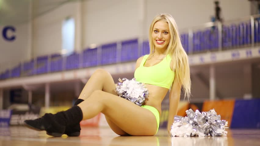 Pretty smiling woman poses with pompoms in empty gym hall - HD stock footage clip