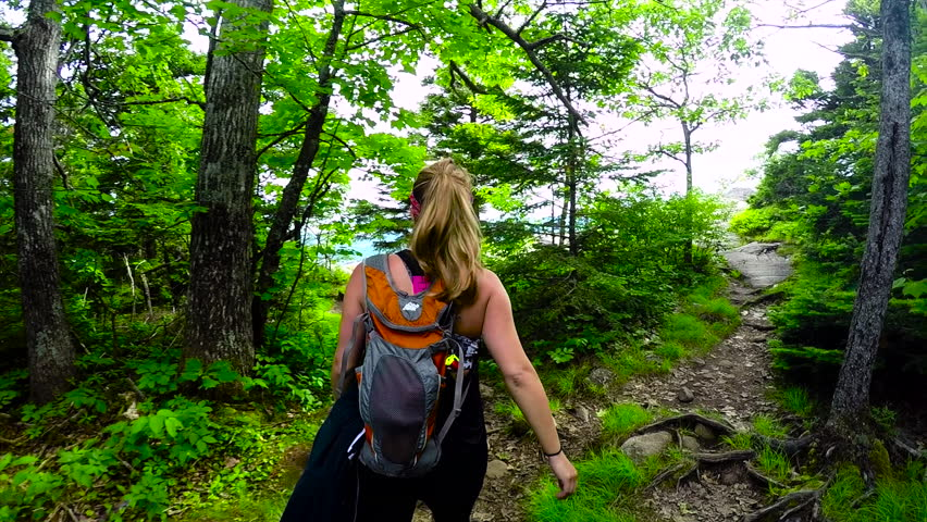 Stabilized tracking shot of a young athletic woman hiking up Camden Hills in Maine on a beautiful summer day. Sunshine through the trees and path to reveal a rock cliff view overlooking the water.