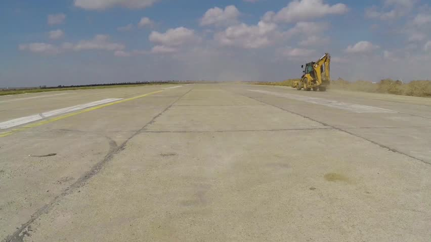 Heavy construction equipment working on an airport runway, aerial view