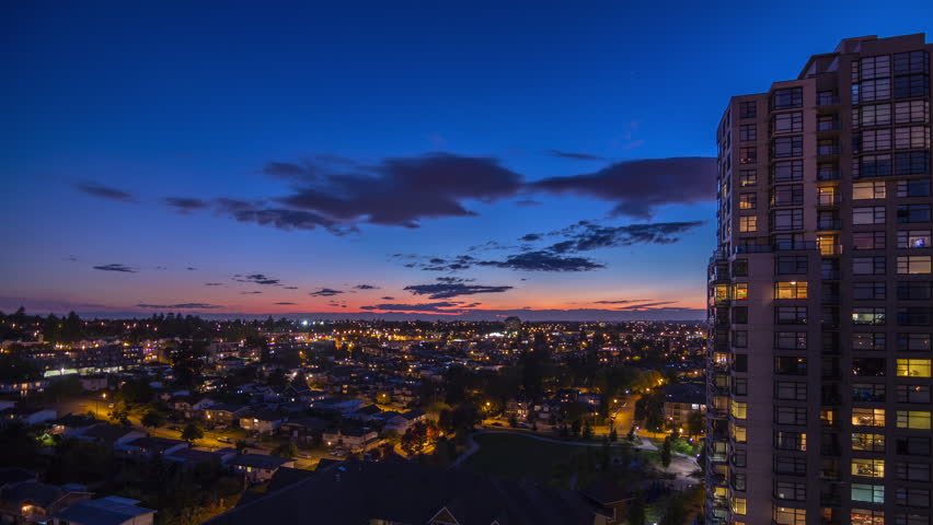 Time lapse of evening night sky with clouds in a residential area fill with houses and apartment building